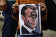 Dieťa drží fotografiu francúzskeho prezidenta Emmanuela Macrona, na ktorej je odtlačok topánky cez jeho tvár počas protestu proti Francúzsku v Istanbule v nedeľu 25. októbra 2020.