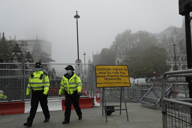 Policajti prechádzajú okolo tabule s odporúčaním pre občanov v súvislosti s pandémiou.