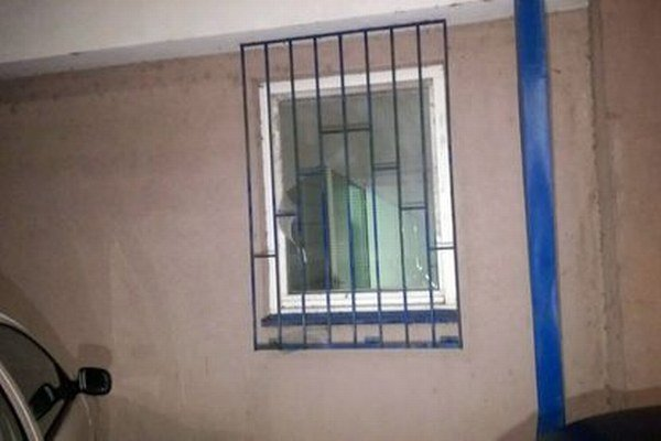 Muž sa mal dostať z budovy von cez toto zamrežované okno. Na fotke vidieť poškodenú sieťku.