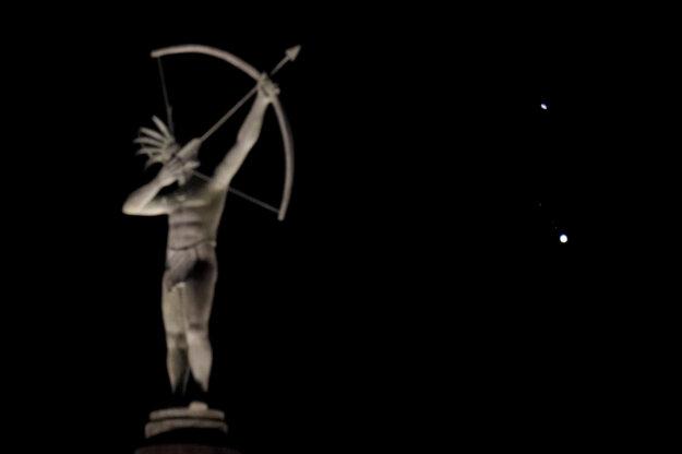 Socha indiána z kmeňa Kansa a planéty Saturn (hore) a Jupiter svietia na nočnej oblohe v americkom meste Topeka.