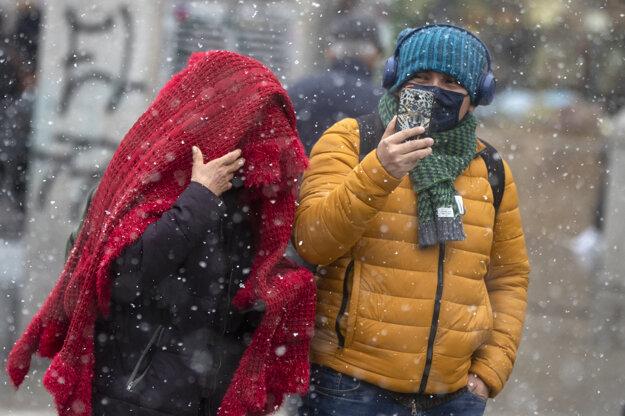Pár kráča ulicou a fotí sa mobilným telefónom počas sneženia v Madride,