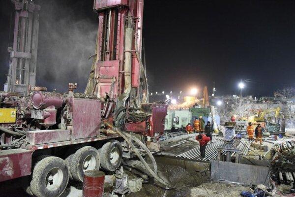 Záchranári vyhlbujú šachtu na mieste explózie v bani na zlato v čínskom meste Čchi-sia 18. januára.