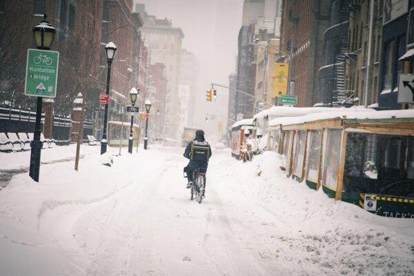 Cyklista prechádza cez zasneženú štvrť Soho na Manhattane v New Yorku.