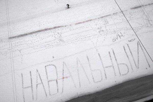 Muž sa bežkuje pozdĺž  zamrznutej rieky Fontanka okolo nápisu Navaľnyj v snehu v Petrohrade.