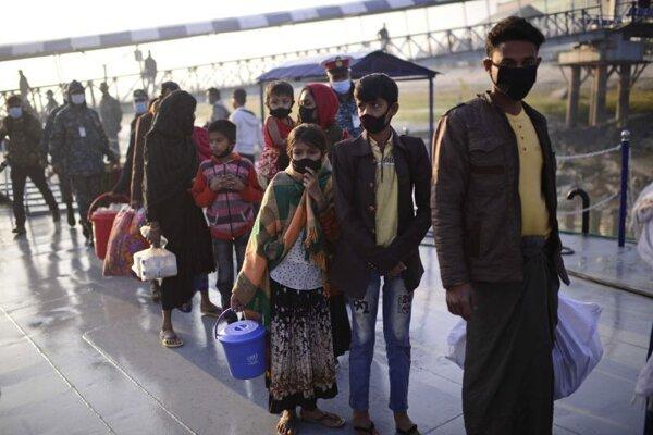 Rohingovia čakajú v rade pri nalodení na námorné plavidlo počas transportu na opustený ostrov z bangladéšskeho prístavu Chittagong v Bengálskom zálive.