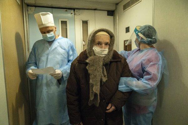 Zdravotní pracovníci v špeciálnych ochranných odevoch pomáhajú staršej pacientke s ochorením COVID-19 v nemocnici v meste Kolomija na západe Ukrajiny.