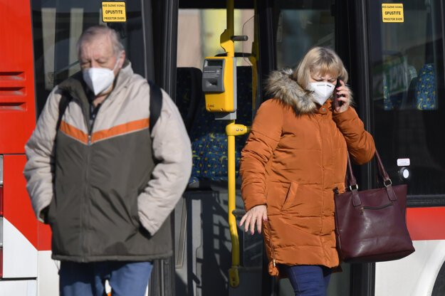 Cestujúci s respirátorom na zastávke MHD v Prešove.