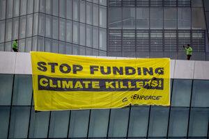 Aktivisti Greenpeace rozvinuli transparent na streche budovy vedľa Európskej centrálnej banky vo Frankfurte nad Mohanom.