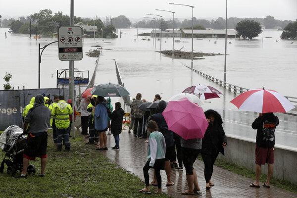 Ľudia sledujú zaplavenú cestu v austrálskom meste Windsor.
