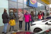 Ľudia  čakajú pred obchodmi, kým sa dostanú dovnútra.