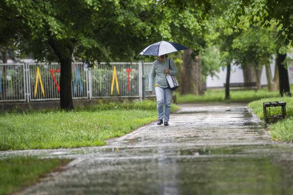 Žena s dáždnikom kráča počas májového dažďa v bratislavskej mestskej časti Ružinov.