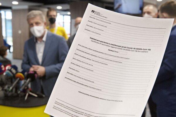 Minister zdravotníctva Vladimír Lengvarský a doklad pre pacienta o zaočkovaní proti Covid-19.