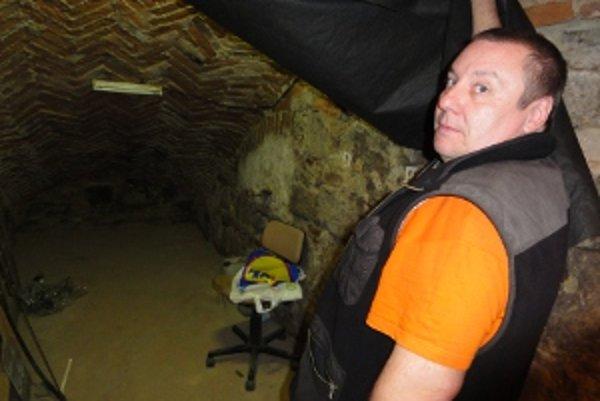 Peter Kereš stojí pri výklenku, z ktorého sa údajne kedysi tiahla jedna z tajných podzemných chodieb.