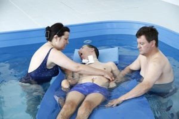 Šimon s rodičmi v bazéne. Terapia trvá hodinu.