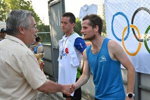 Riaditeľ pretekov Ján Jacoš (vľavo) blahoželá víťazovi v hlavnej kategórii.