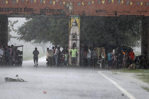 Ľudia sa skrývajú pred dažďom pod mostom v meste Prajágrádž.