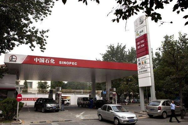 Motoristi tankujú na benzínovej pumpe spoločnosti Sinopec v Pekingu.