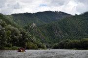 Skupina turistov splavuje rieku Váh. V pozadí vidieť Starhrad neďaleko obce Strečno.