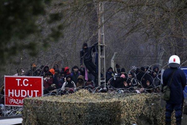 Príslušník gréckej poriadkovej polície hliadkuje pri pohraničnej bráne, cez ktorú sa pokúšajú prejsť migranti v dedine Kastanies na grécko-tureckej hranici 29. februára 2020.