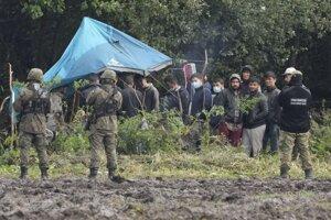 Poľské bezpečnostné zložky hliadkujú pri skupine migrantov na hraniciach s Bieloruskom.