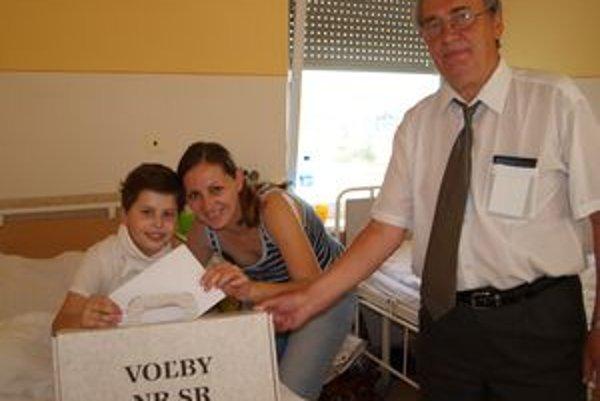 V nemocnici v Nitre volila aj Elena Gažiková so synom Tomášom. Vpravo člen okrskovej volebnej komisie Gejza Rácz.