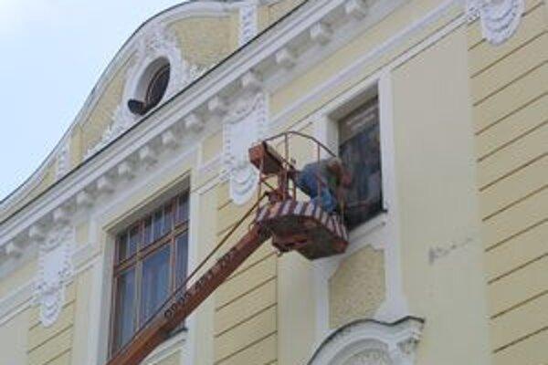 Reprodukcie obrazov inštalovali na oknách Nitrianskej galérie pomocou plošiny.