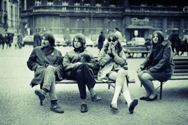 Vlasáči so svojimi kamarátkami na Hviezdoslavovom námestí pred hotelom Carlton. V roku 1968 na chvíľu prestali byť dlhé vlasy tabu, s nástupom normalizácie sa šikanovanie pre dlhé vlasy opäť začalo.
