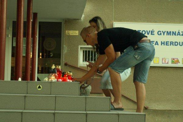 Študenti prichádzajú, aby na schodoch gymnázia zapálili sviečky.