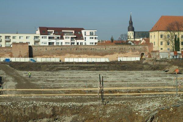 Tam, kde je dnes len jama, by už o rok malo stáť obchodné centrum a štadión.