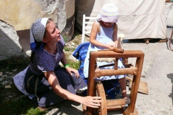 Jana Michalíková ukazuje techniku pradenia aj malej návštevníčke jarmoku.