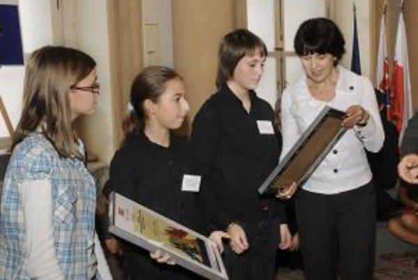 Mária Tekelová (vpravo) z ministerstva školstva odovzdáva ocenenie v kategórii pomoc rovesníkom zástupcom kolektívu žiakov siedmej triedy zo Základnej školy J. A. Komenského z Bánoviec nad Bebravou.