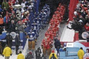 Hráči Toronta v modrom a Detroitu v červenom vstupujú na ľad na štadióne University od Michigan.