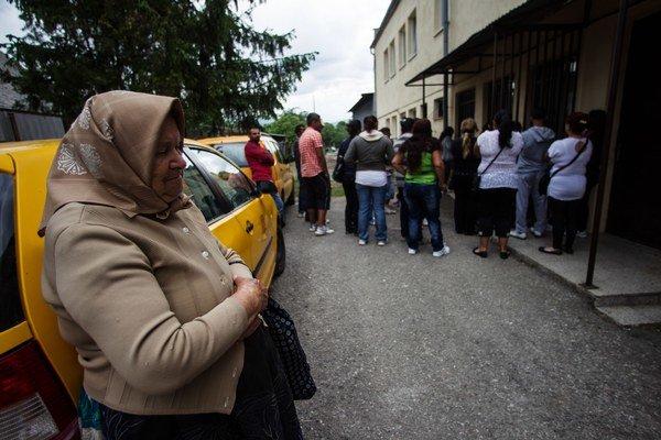 Ľudia v Kecerovciach si preberajú dávky zo zadného vchodu pošty.