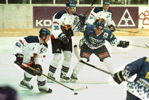 Hokejisti Slovana Bratislava sa 21. septembra 1999 v Bratislave<br>stretli v úvodnom zápase nového ročníka Európskej hokejovej ligy s rakúskym tímom HC Heraklith Villach. Na snímke zľava Ľubomír Kolník a Miroslav Hlinka v súboji o puk s Bradom Purdiem.