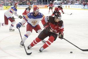 Sidney Crosby sa snaží udržať puk na hokejke pred brániacim Jevgenijom Dadonovom.