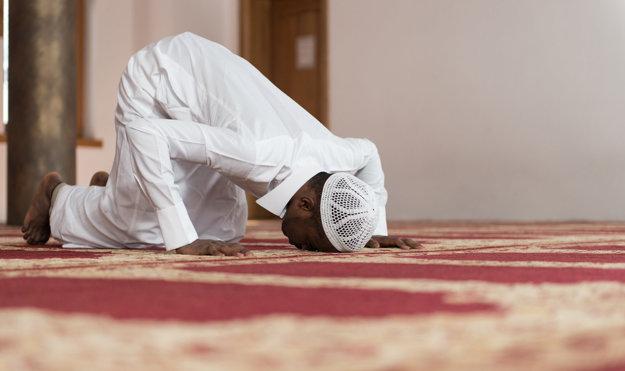 Africký moslim sa modlí k Bohu, na sebe má tradičnú prikrývku hlavy.