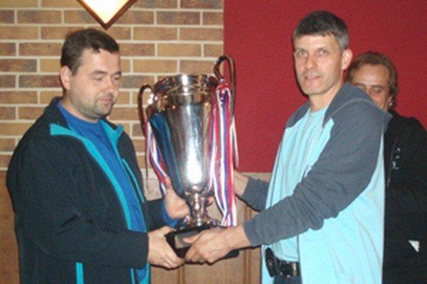 Vľavo Jozef Bocko preberá pohár pre víťazov od predsedu ligy Romana Nistlera.