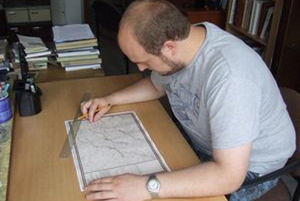 Historik Martin Turóci skúma staré mapy.