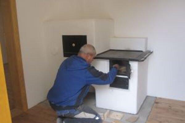 Ladislav Perďoch, ktorý pracoval so svojím tímom  na rekonštrukcii domčeka, sa snaží podkúriť v dobovej peci.