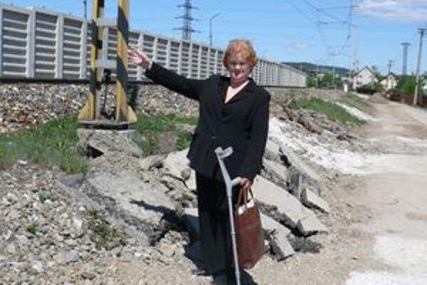 Jedna z obyvateliek Svrčinovca ukazuje na betónový múr, ktorý rozdelil obec.