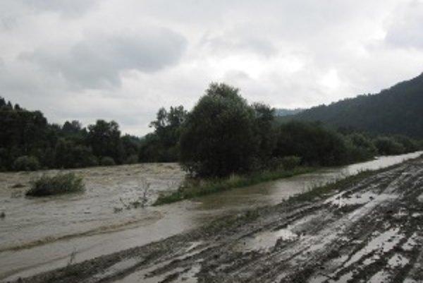 Rozbúrená rieka. Opäť sa vyliala na komunikáciu, ktorá spája dve obce - Dunajov a Ochodnicu.