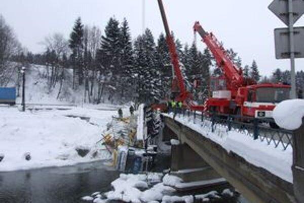 Záchranári vyslobodzujú kamión, ktorý v nedeľu pred polnocou spadol z mosta v Staškove do Kysuce.