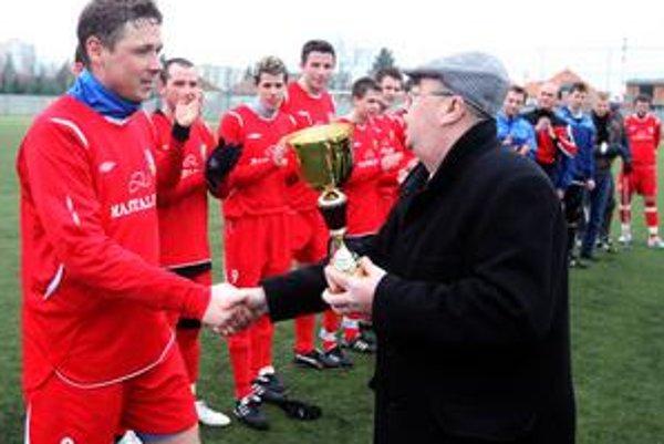 Kapitán OFK Dunajská Lužná Maroš Puchner preberá z rúk predsedu Bratislavského futbalového zväzu Andreja Machoviča trofej pre víťaza Zimného turnaja BFZ seniorov.