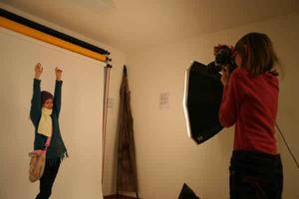Dve malé účastníčky kurzu v ateliéri pri fotení jednej z tém. Deti pracujú s profesionálnou fototechnikou.
