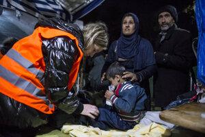 Dobrovoľníčka skúša, či dieťaťu budú pohodlné darované topánky.