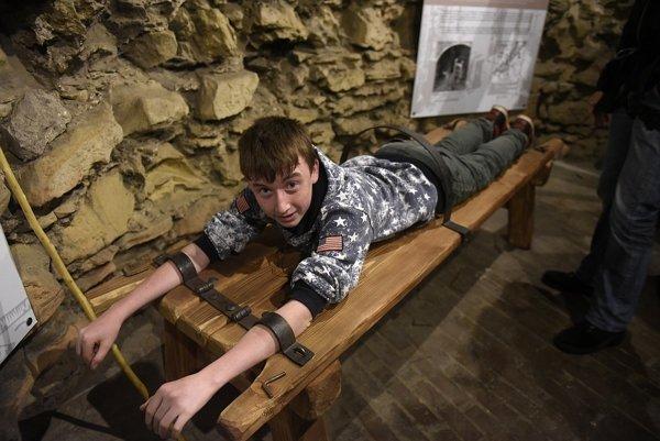 Chlapec leží na dereši (lavica, na ktorú odsúdeného pripútali na trest bitím) v objekte hladomorne, novej stálej expozícii Trenčianskeho hradu.