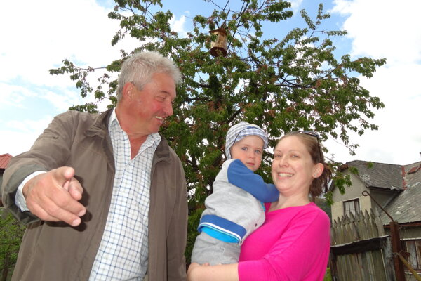 Jozef Mikušík v záhrade v Brvništi s vnukom Filipkom a nevestou. Vzadu strom s búdkou, ktorá je pripravená pre sovu.