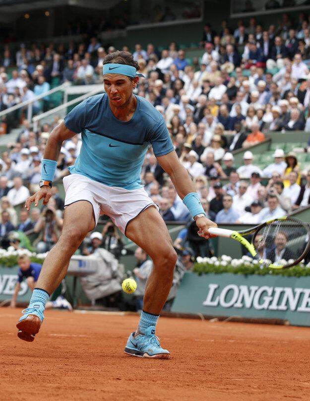 Rafael Nadal odvracia loptičku úder pomedzi nohy.