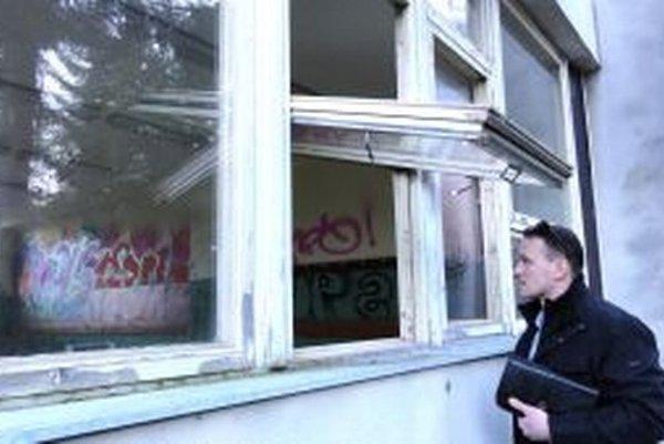 Peter Košík pozerá dovnútra cez okno, ktoré sme našli dokorán otvorené. Aj spoza skla vidieť, že sa dnu už vybláznili sprejeri.