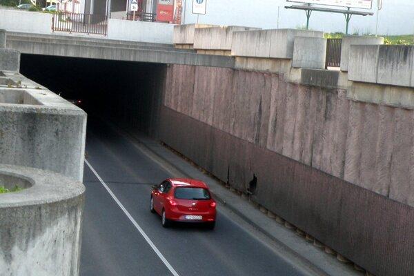 Autá vchádzajú do tmavého podjazdu, väčšina lámp v ňom nesvieti.